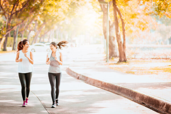 Two happy beautiful healthy Asian girlfriend jogging together outdoor in park during summer